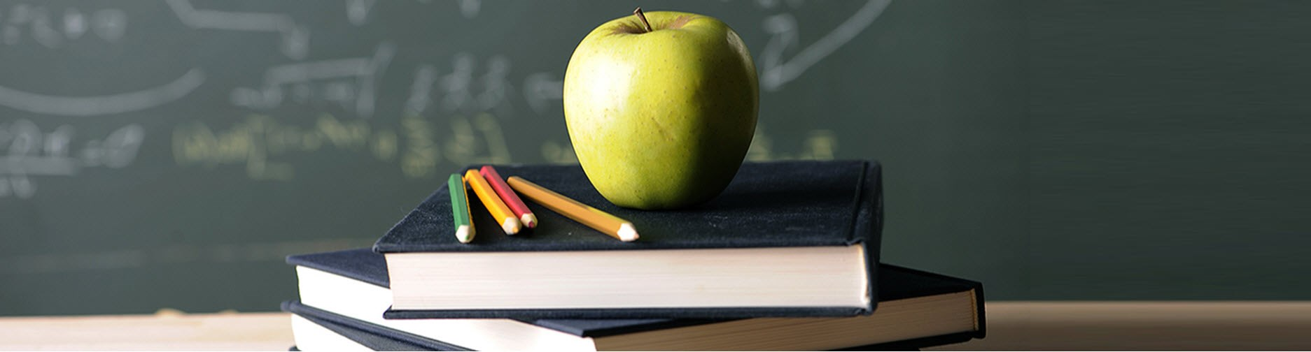 Apple with pencils and books